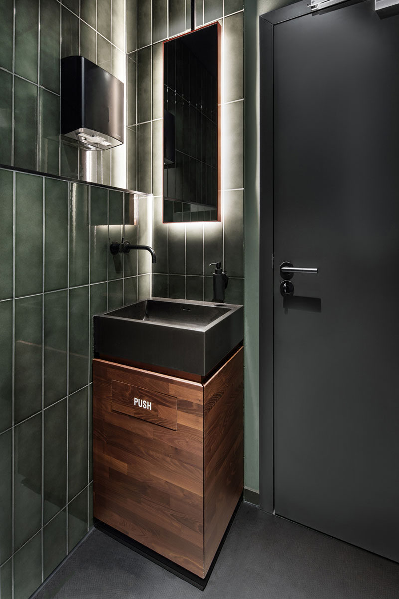 In this small bathroom, green tiles, wood and a backlit mirror reflect the design choices in this modern bar.