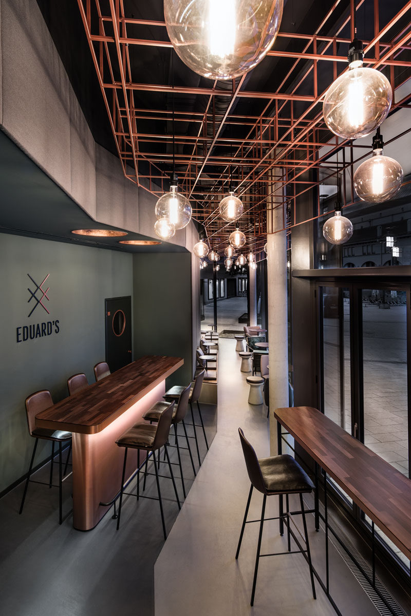 This modern bar has window seats that allow people to have a drink and watch the activities outside. The ceiling installation in the 16 foot (5m) high space consists of angular copper rods and eye-catching bulbs.