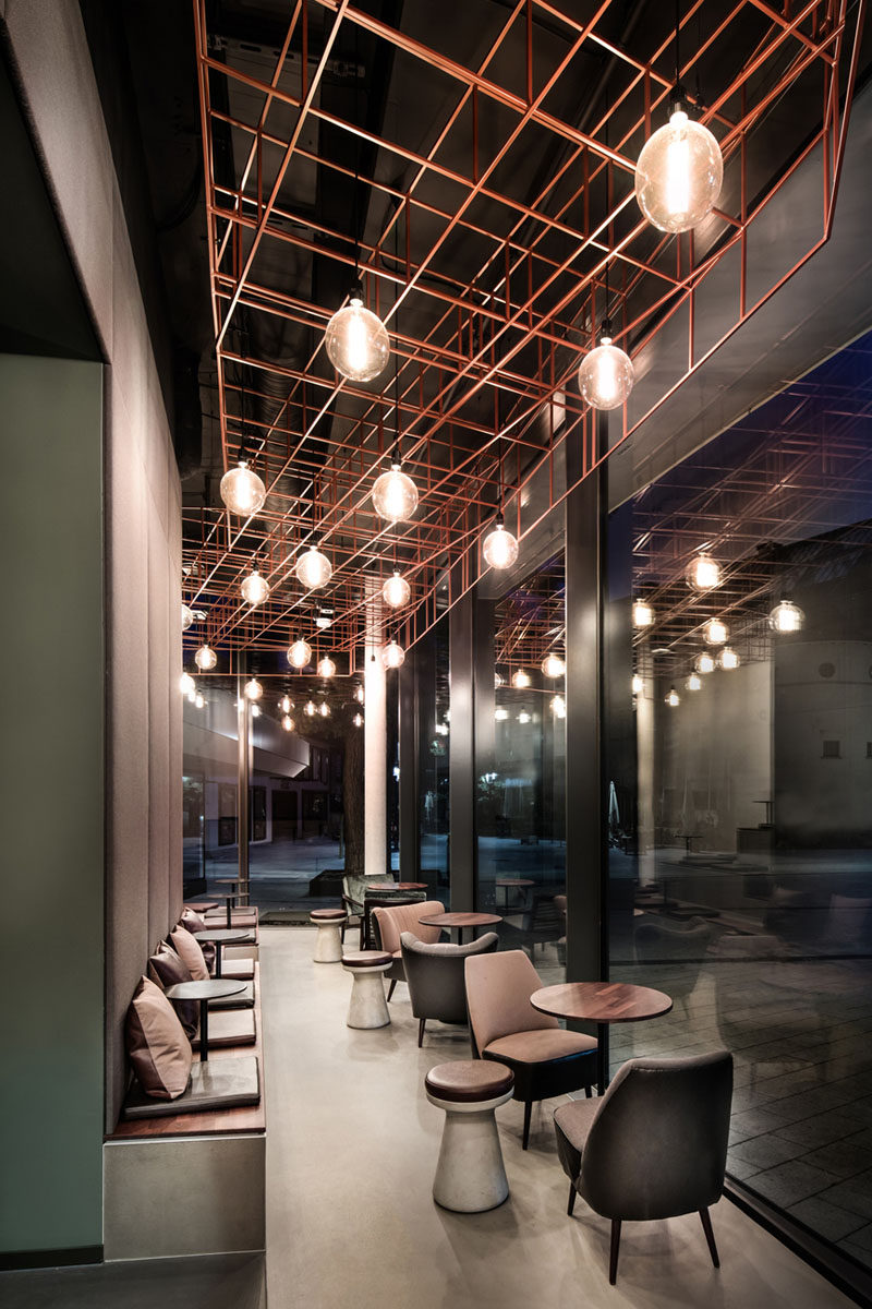In this modern bar, one wall has a line of benches that use it as a backrest, while closer to the window, there's armchairs, both of which look out onto the outdoor patio.
