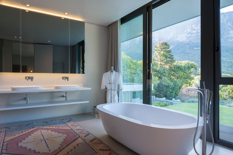 In the bathroom, a mirror with hidden lighting creates a calming atmosphere and the freestanding bathtub sits in front of the floor-to-ceiling windows to take advantage of the view.