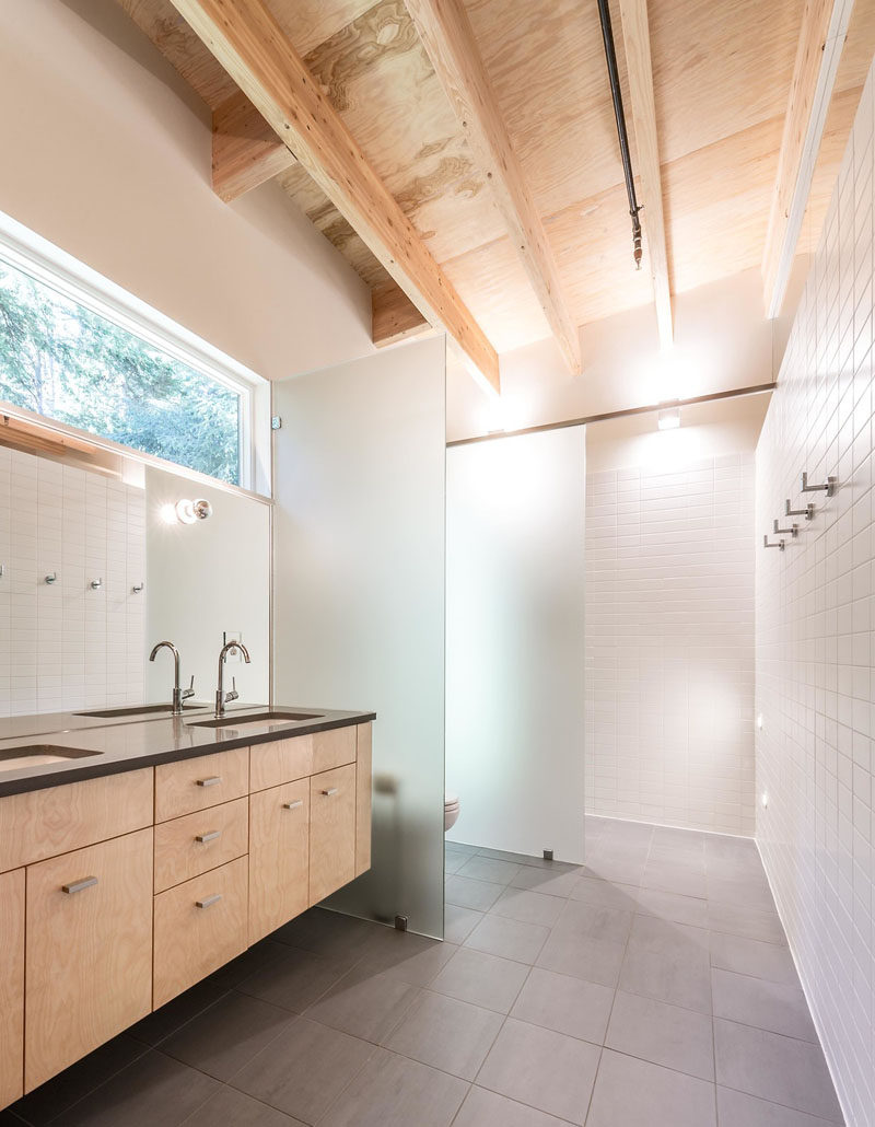 In this simple and modern bathroom, frosted glass partitions have been used to separate the toilet and the shower from the rest of the space.