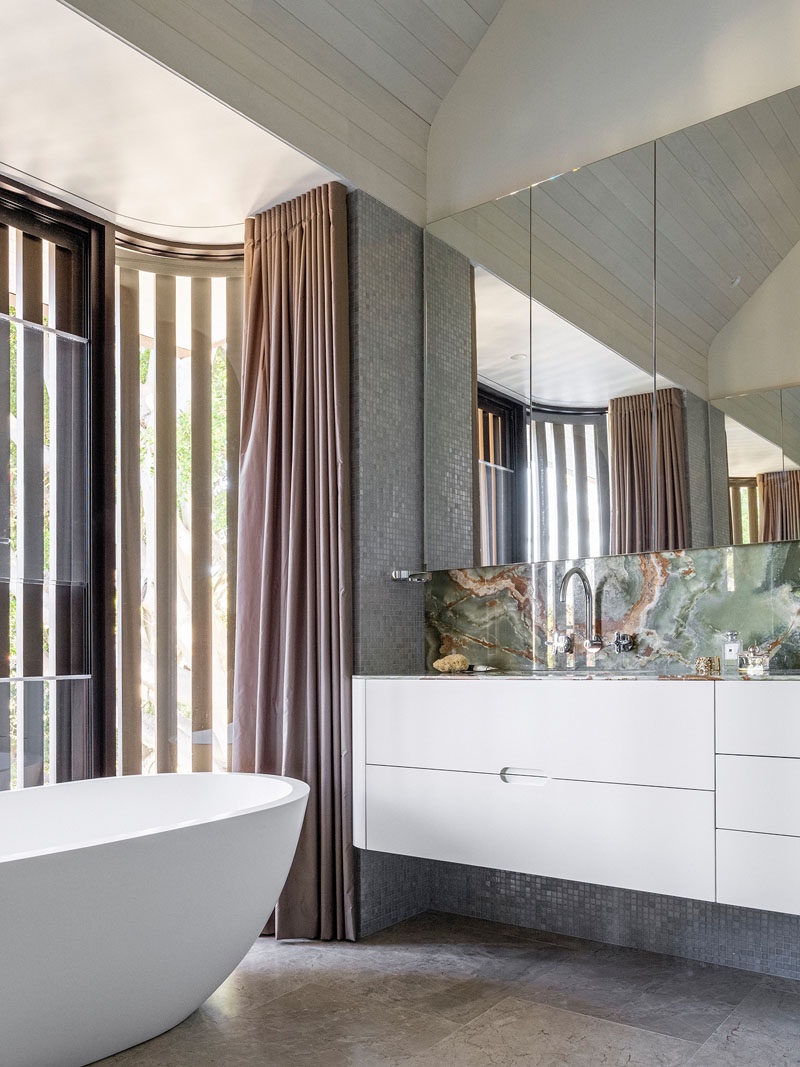 In this bathroom, green onyx has been used for a backsplash, while a white vanity and oval bathtub add a simple contemporary touch.