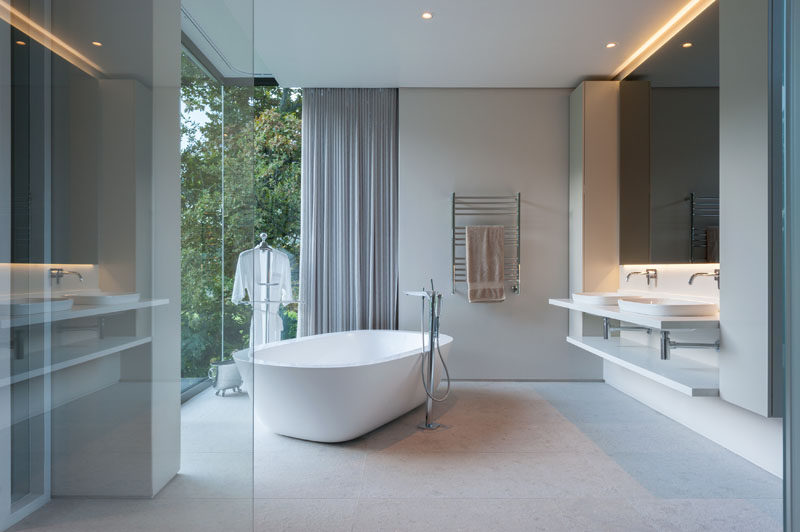 In this modern bathroom, a mirror with hidden lighting creates a calming atmosphere and the freestanding bathtub sits in front of the floor-to-ceiling windows to take advantage of the view.