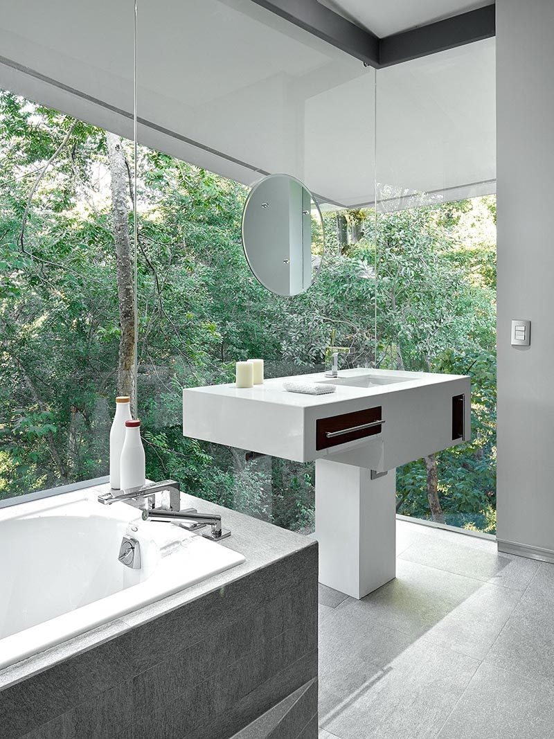 This modern bathroom features floor-to-ceiling glass walls that provide a view of the forest outside.