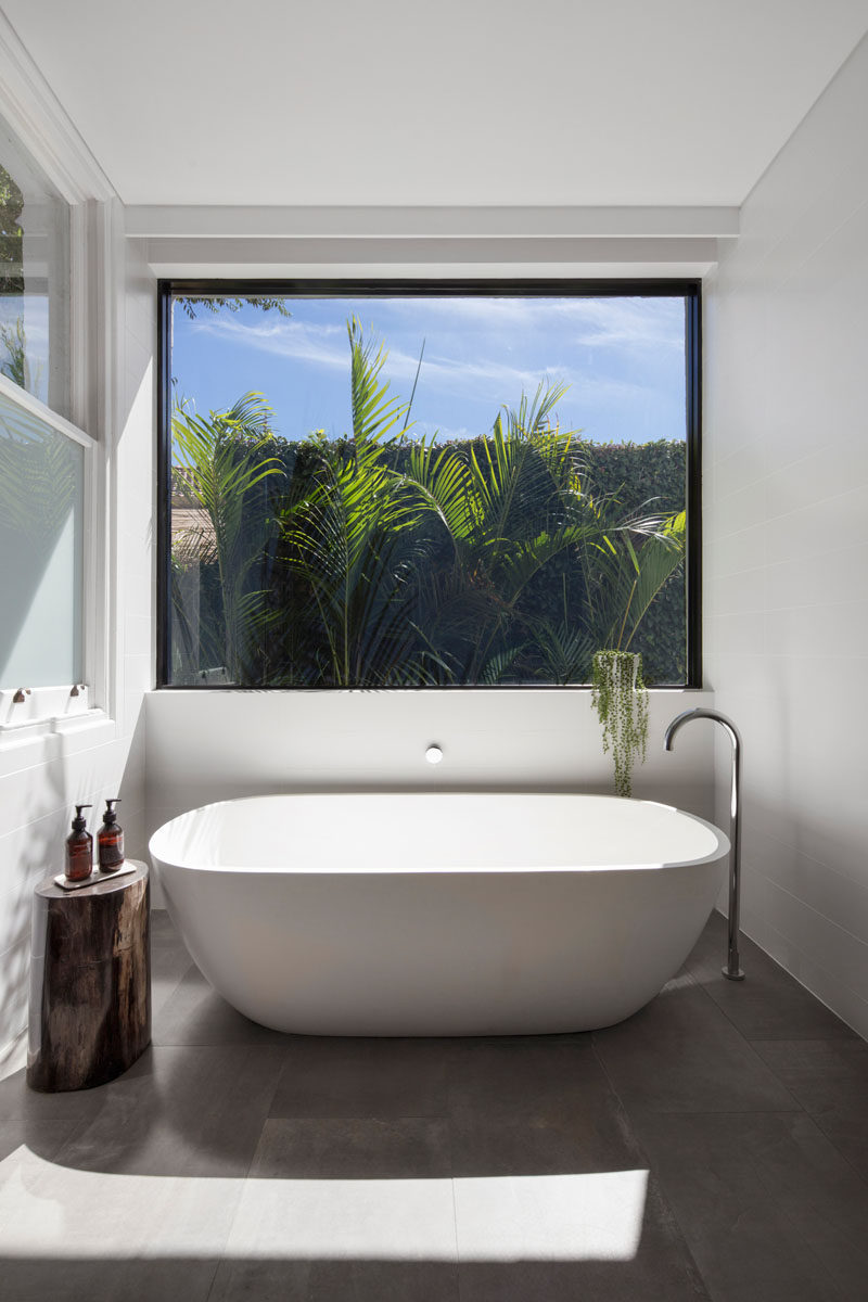 This modern bathroom extension has a large window that sits above a freestanding bathtub.
