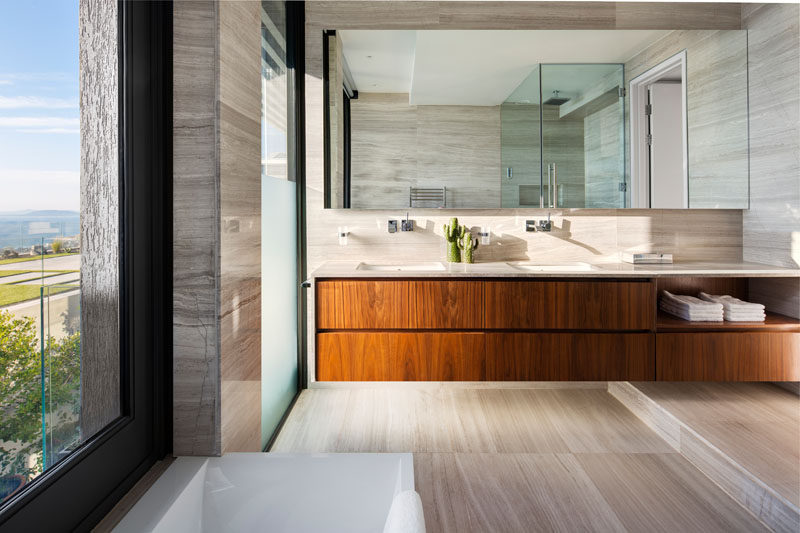 In this modern master bathroom, a long wood floating vanity with dual sinks provides storage, while windows provide water views.