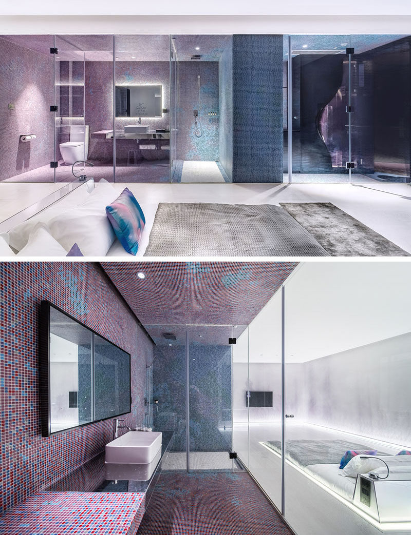This futuristic modern hotel room features a sunken bed in the middle of the room. The bed sits flush with the floor, with only the headboard rising up from the floor.