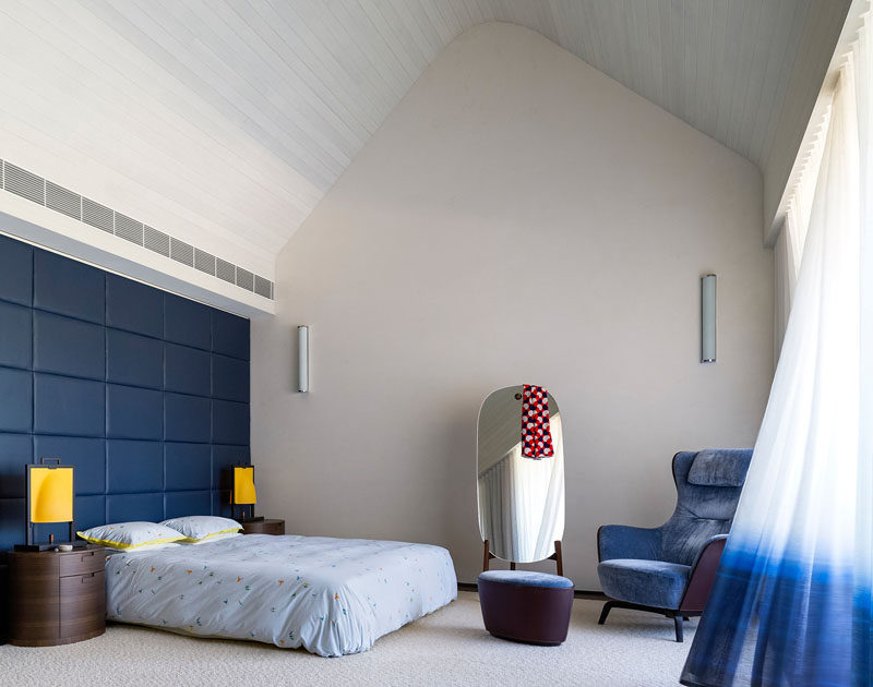 In this contemporary master bedroom, the double height ceiling features whitewashed timber boards, giving it a lofty appearance.
