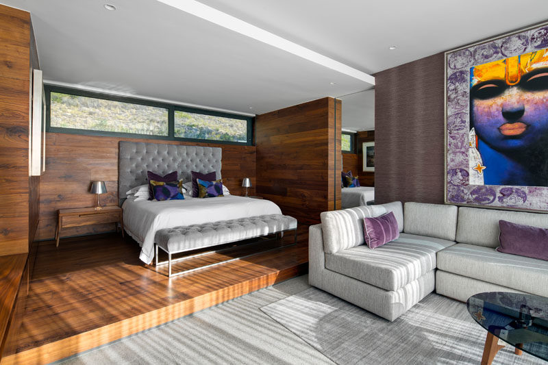 In this modern master bedroom, the bed sits slightly raised on a wood platform, which a grey couch provides a nice spot to relax.