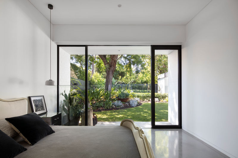 This simple white bedroom with concrete floors, opens up to a modern landscaped backyard with swimming pool.