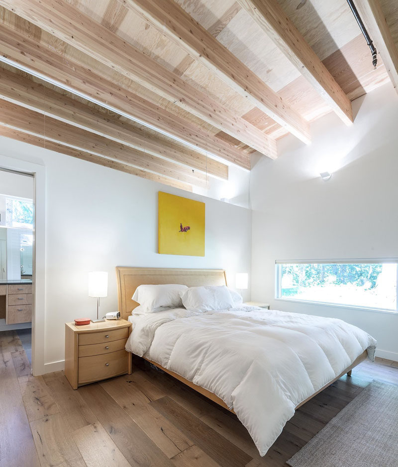 In this modern bedroom, high ceiling create a sense of openness, while the white walls are broken up with a bright yellow piece of artwork.