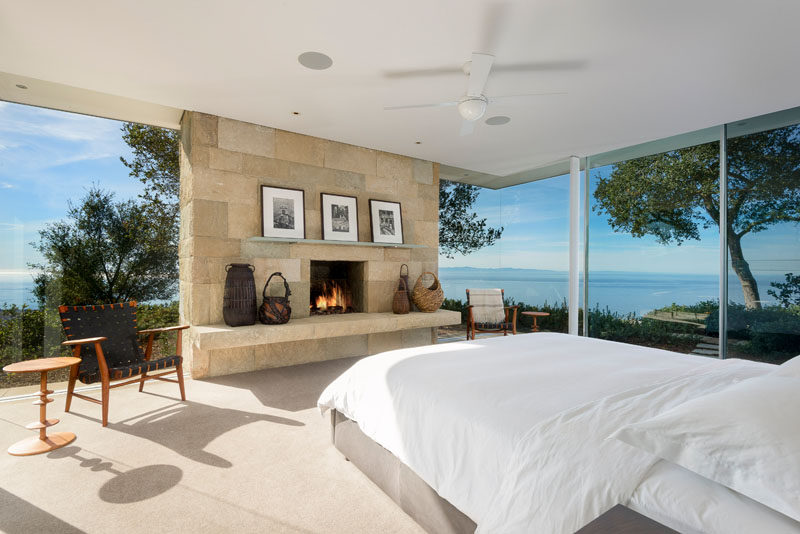 The modern master bedroom has its own stone fireplace and amazing water views.