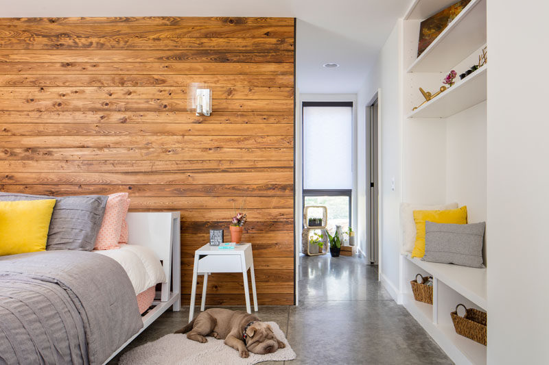 In this modern master bedroom, a wood accent wall adds warmth to the mostly white room, while open shelving and a bench have been built into the wall.