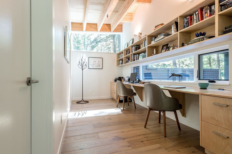 In a hallway next to one of the bedrooms in this modern house, there's a small home office area. Built-in furniture and shelving makes the space suitable for two people and a window provides views outside.