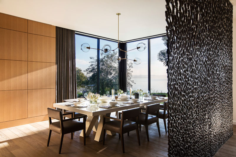 Large floor-to-ceiling windows allow plenty of natural light to fill this modern dining room. #Windows #BronzeScreen #DiningRoom