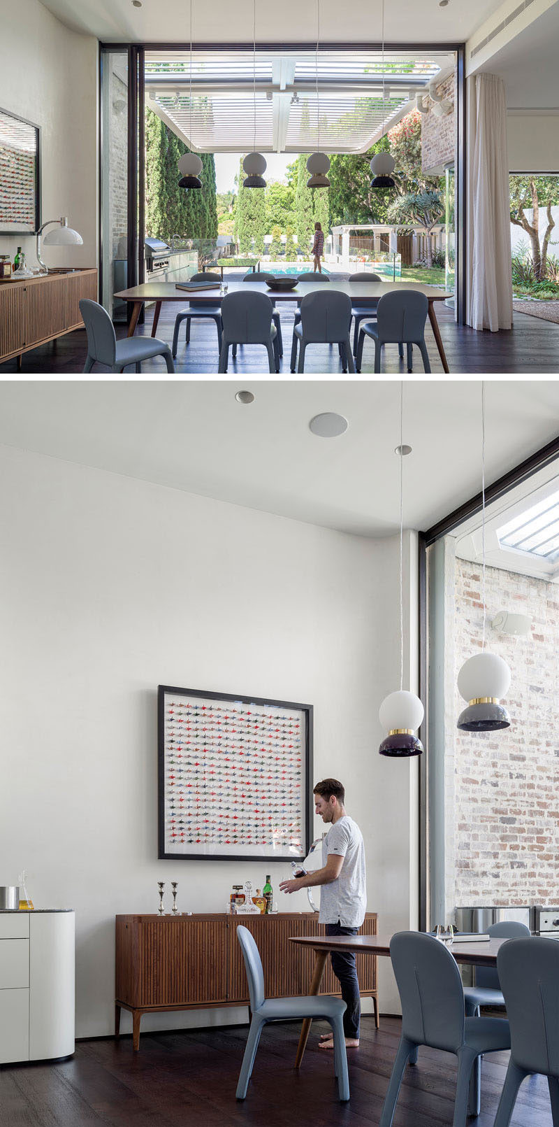 This modern dining room features 13 foot (4m) high glass doors that slide away into a wall cavity to create an unobstructed flow into the garden. High ceilings make the interior of the home feel open and airy.