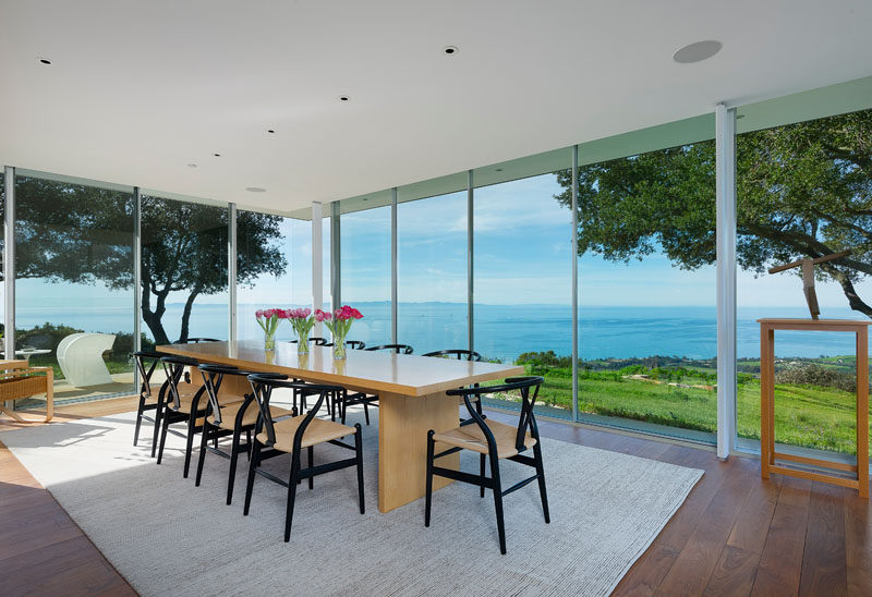 In this modern dining room, glass walls provide an uninterrupted view of the garden and ocean.