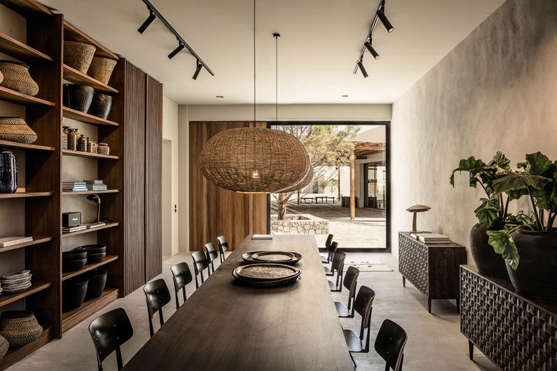 This contemporary hotel in Greece has a library with a large table, floor-to-ceiling shelving and access to a courtyard. #Library #Shelving #Hotel #Greece #InteriorDesign