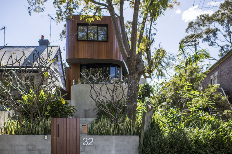 . A Curved Wood And Concrete Exterior Greets Visitors To This Home In