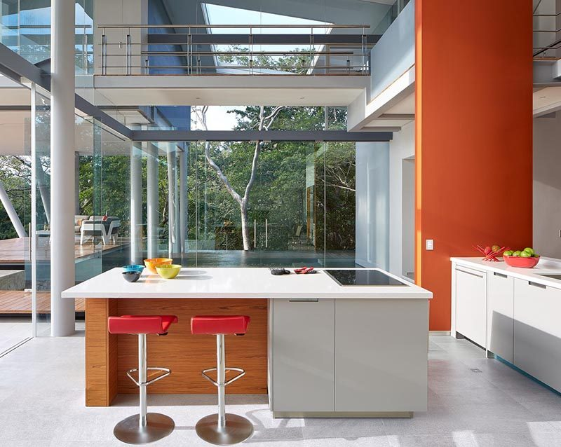 This small and modern kitchen has minimal cabinets, with the island home to the oven and cooktop. A bright orange wall adds a pop of color to the space.