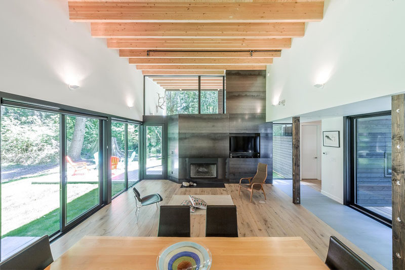 Design as a zen-like retreat from the city, the interior of this modern house features high ceilings that make the interior feel large and open. Exposed wood beams and a steel clad fireplace add warmth to the space, while windows let in plenty of natural light.