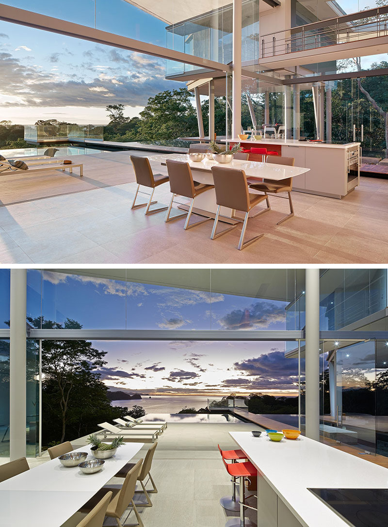 Separating the living room from the kitchen in this modern house, is the dining area. A simple white dining table is surrounded by tan dining chairs, and the dining area opens up to the deck and pool.