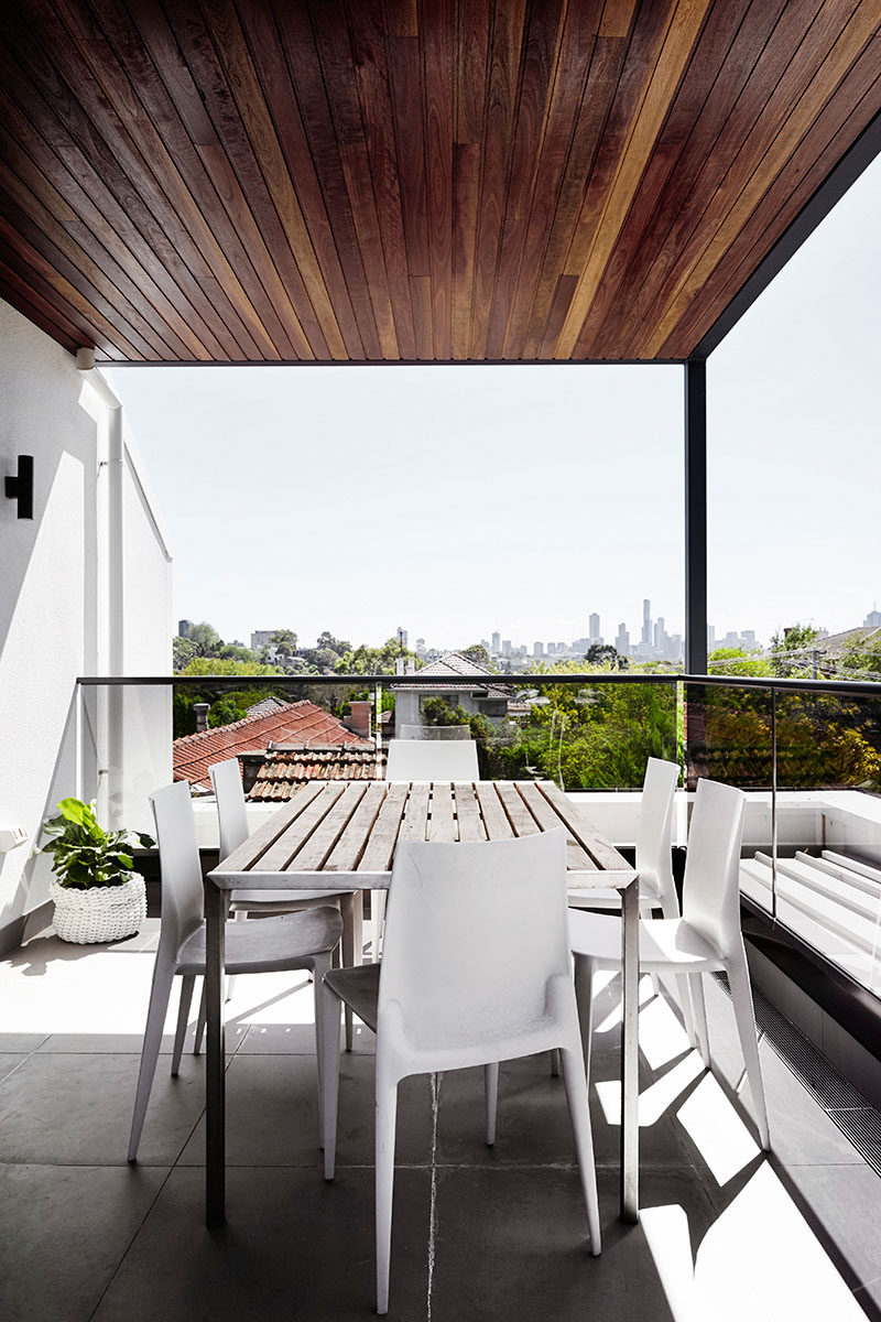 This wood covered rooftop deck has views of the neighborhood and city in the distance.