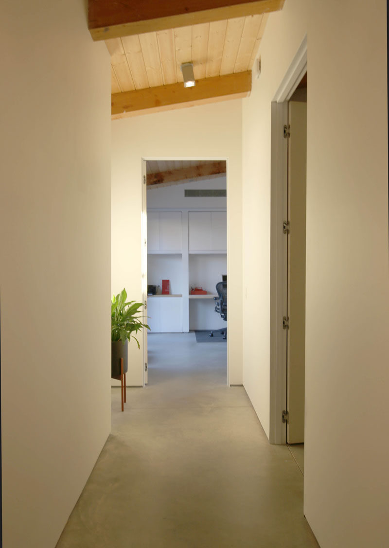 A simple hallway with concrete floors leads to the bedrooms in this modern house. #ConcreteFloors #InteriorDesign #hallway