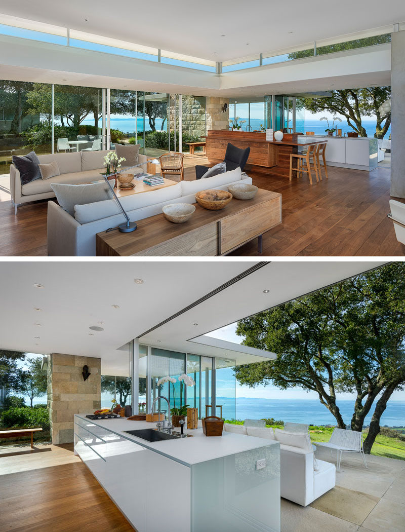 The living room and kitchen in this modern house share the same space, and sliding glass doors open up to outdoor sitting areas.