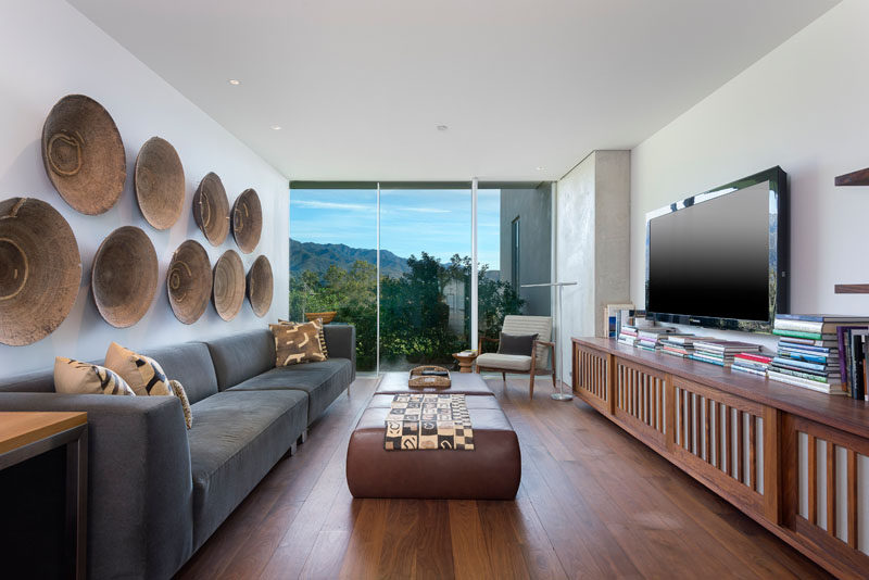 In this dedicated tv room, wooden artwork hangs on the wall opposite a wood tv cabinet, and a window provides a picture perfect view of the mountains.