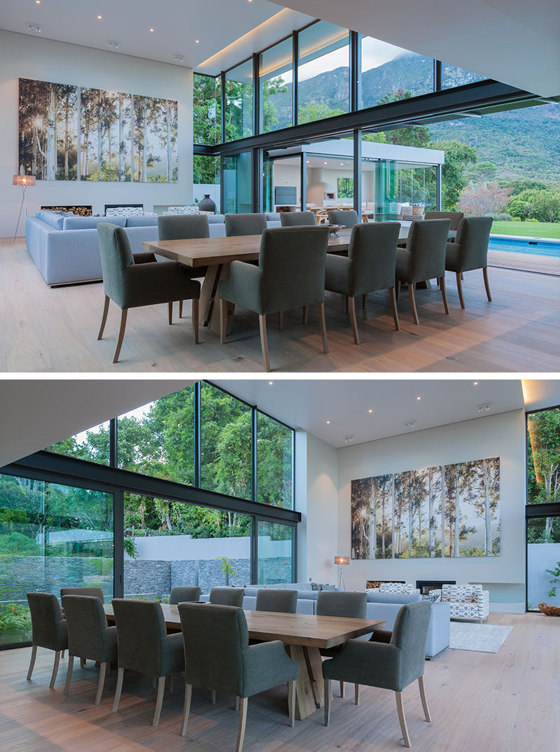 Large sliding glass doors can be opened on either side of this modern double height combined living and dining room. On one side is the swimming pool and on the other is a courtyard surrounded by a stone wall.