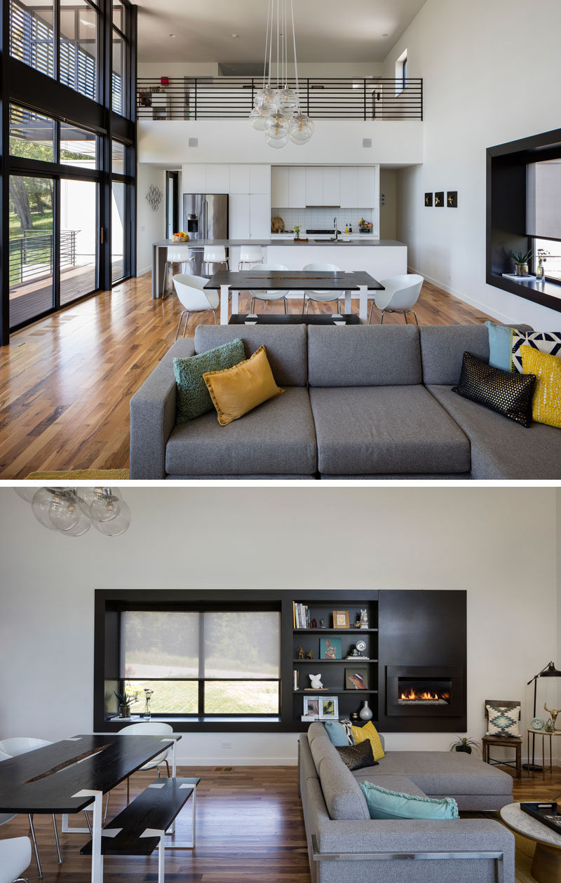 This modern house has an open plan living area with a black framed window seat with open shelving and a fireplace built into the wall.