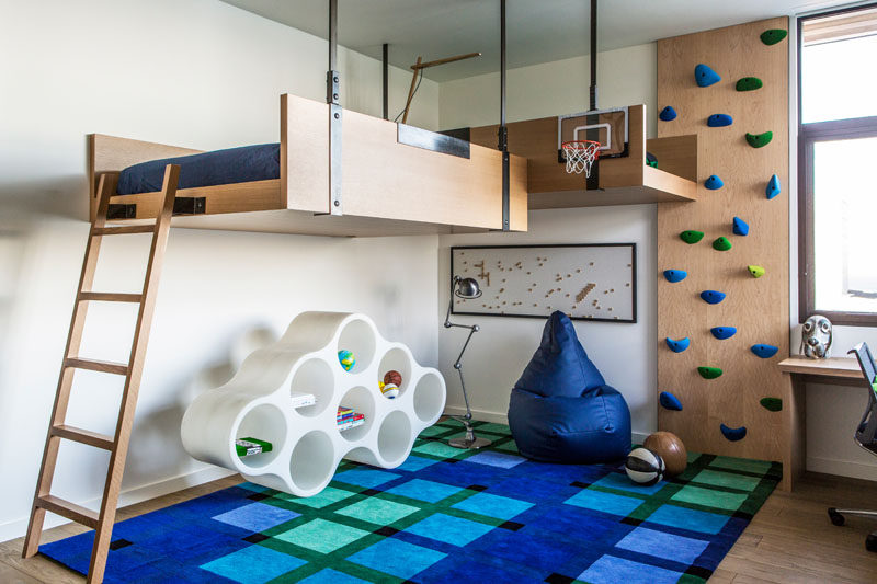 In this modern kids bedroom, there's two beds that are mounted to the wall and hang from the ceiling. To reach the beds, there's a ladder or a rock climbing wall.