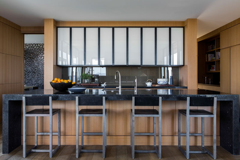 This modern kitchen has a large stone island with a wood base and plenty of room for seating.