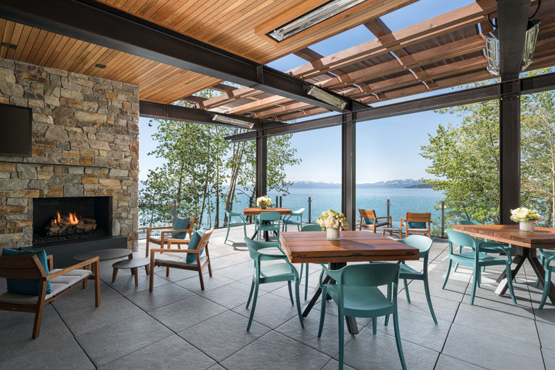 The upper floor of this modern lakeside club house features a fireplace with a stone surround, and a covered dining deck with expansive views of the lake.