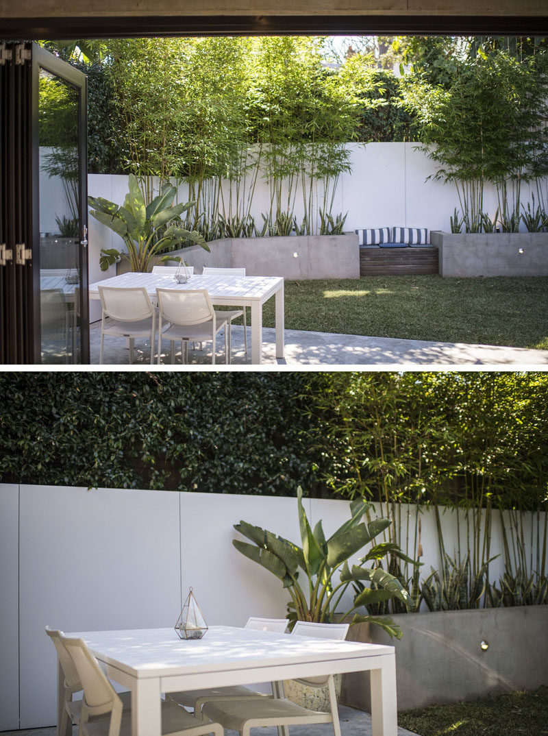 This modern landscaped backyard has custom planters that wrap around wall, a built-in wood bench and an outdoor dining area. #BuiltInPlanters #Landscaping #Backyard #ModernBackyard