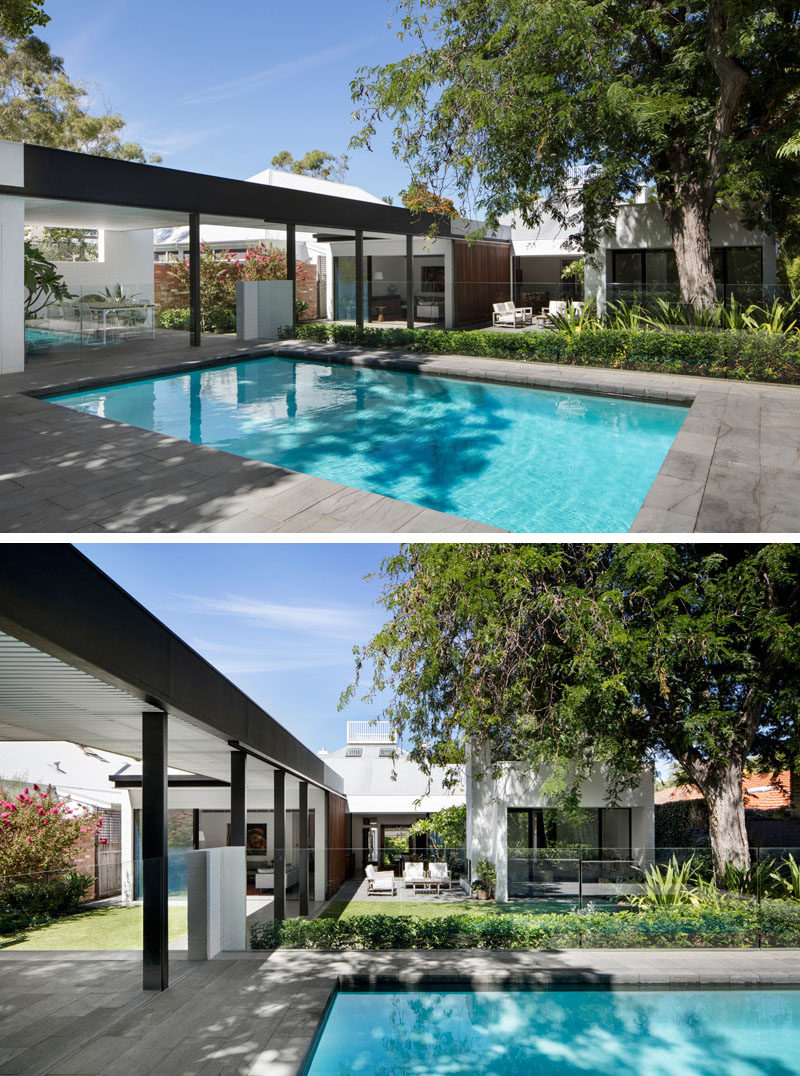 Next to the outdoor kitchen and dining area in this modern backyard is the swimming pool. A glass safety fence surrounds the pool and allows for uninterrupted views of the backyard.