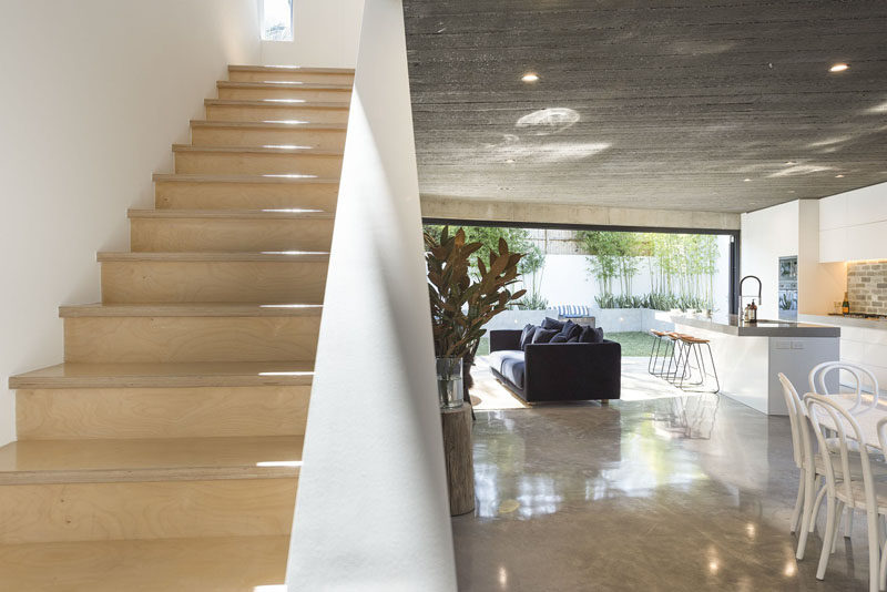 This modern house with concrete floors and ceilings features light wood stairs that lead up to the second floor of the home. #ModernHouse #LightWoodStairs #Stairs #Concrete #ConcreteFlooring #ModernInterior