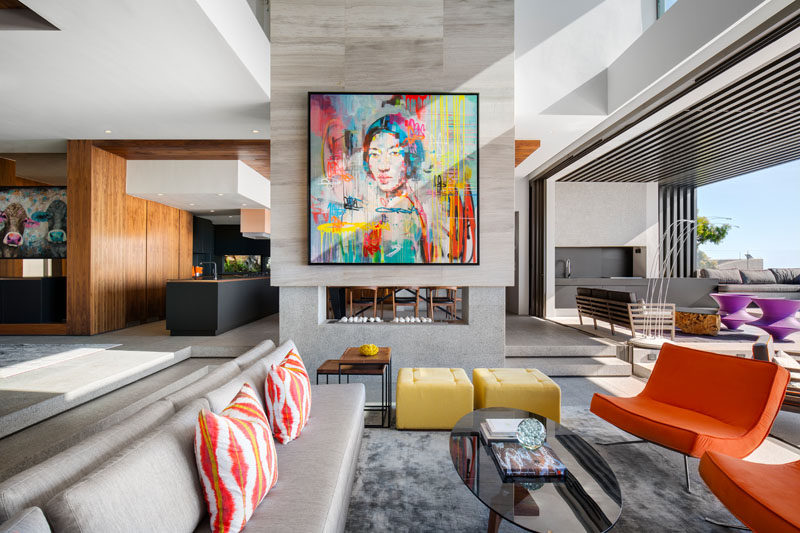 In this modern living room, there's a double-sided fireplace with a bright colorful piece of artwork to draw your attention. This also compliments the other brightly colored furnishings in the space.