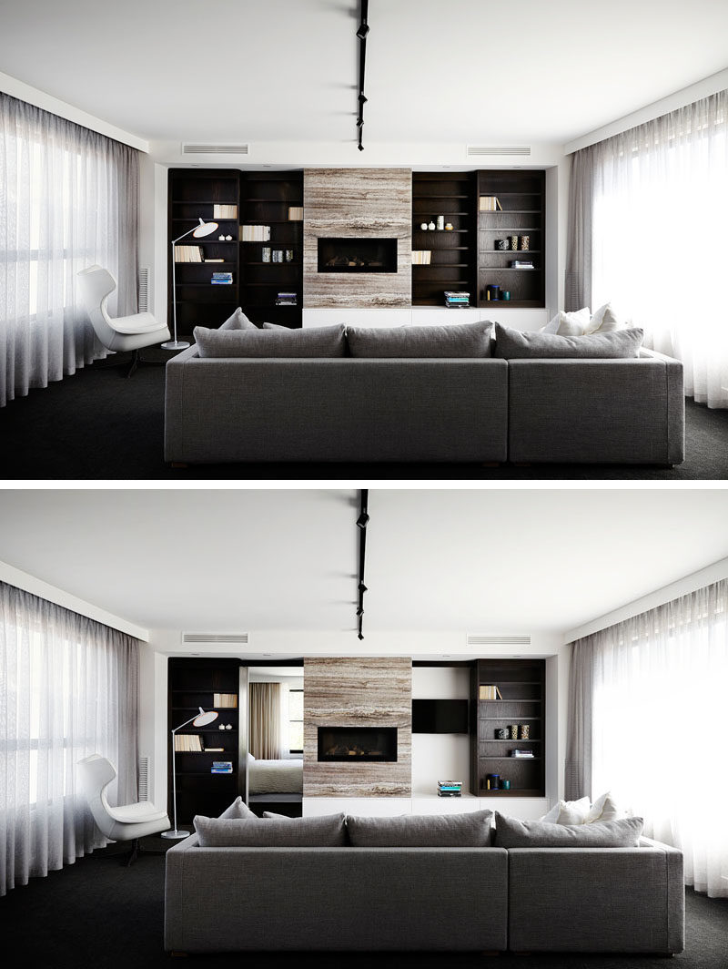 On the second floor of this modern house, there's living room with large windows covered by billowing curtains, and wood shelving on either side of the fireplace slide open to reveal a hidden bedroom and the television.