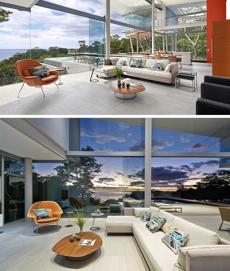 The main living space in this modern house is open plan, with the living room at one end. The floor-to-ceiling glass walls ensure that the view can always be enjoyed, and the single orange armchair ties in with the orange paint and stools used in the kitchen.