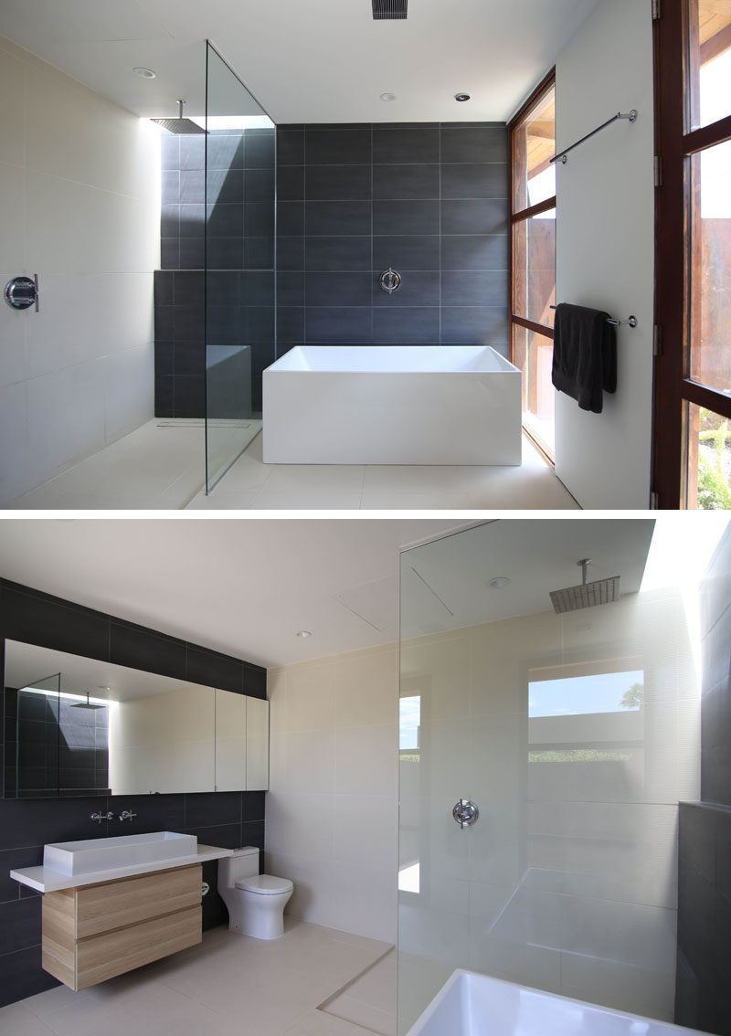 In this master bathroom, dark tiles have been used to create an accent wall, while a glass partition separates the shower from the bathtub. The dark tiles have also been used on the wall behind the mirror and vanity. #MasterBathroom #EnsuiteBathroom #DarkTiles #ModernBathroom #bathroom