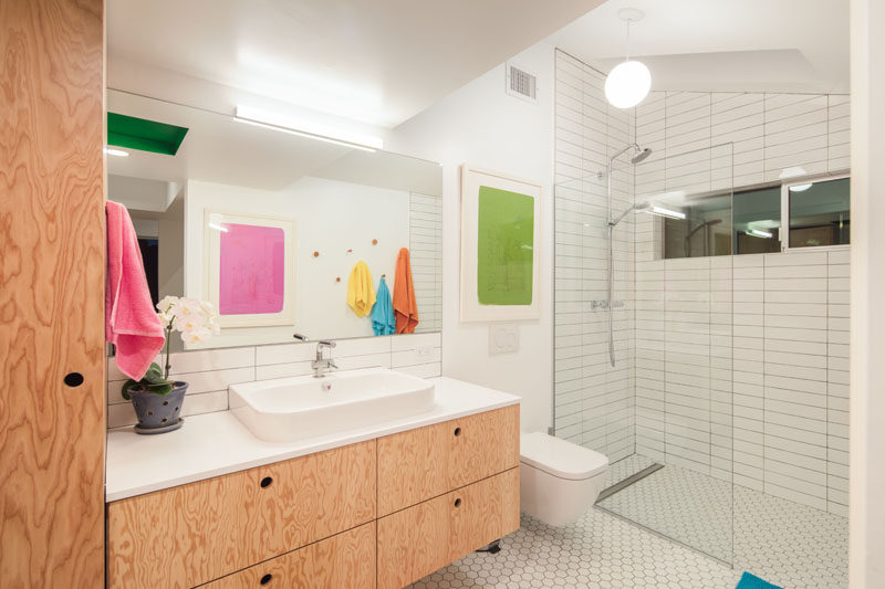 In this modern master bathroom, wood cabinets and a vanity provide storage, while while tiles have been used in the shower and a glass partition help the light travel throughout the room.