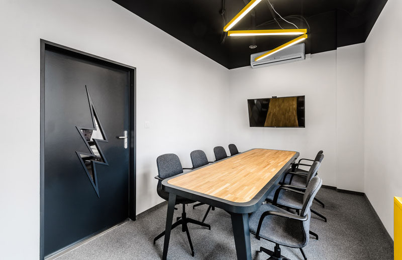 In this modern office, lightning bolt inspired elements can be found in the boardroom with the overhead lighting and the window shape in the door.