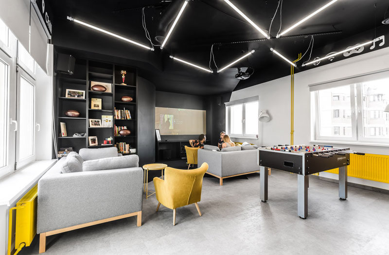 In this modern office break room, zig-zag shaped lamps hang from the ceiling, and the yellow furniture elements tie in with the lightning bolt in the company's logo.