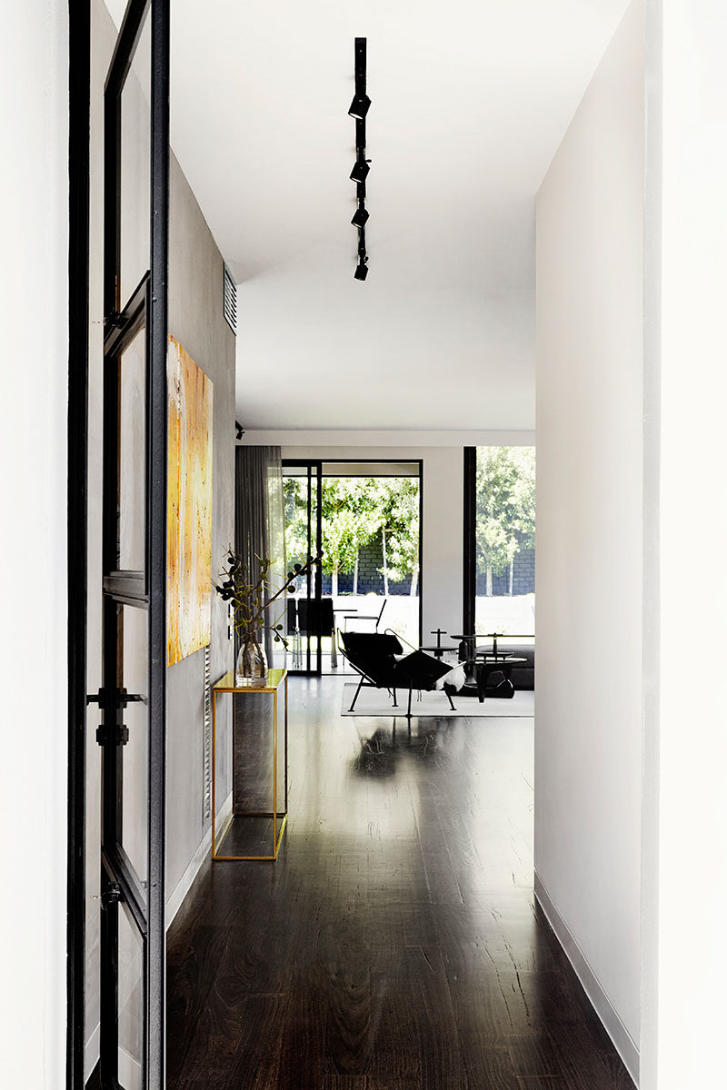 Stepping inside this modern house, white walls have been combined with dark wood floor and black elements for a contemporary and minimalist interior.