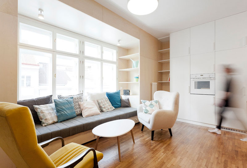 Instead of buying furniture separately and having an odd space in the living and kitchen area of this apartment, the designers created a dedicated space for lounging by using wood to create a built-in couch and shelving. #Couch #LivingRoom #InteriorDesign #BuiltInCouch #Sofa #BuiltInFurniture