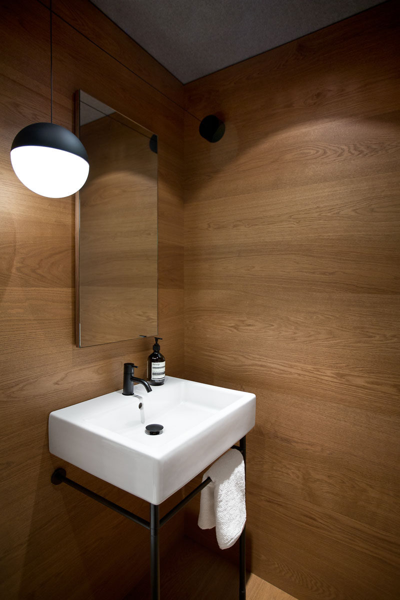 In this modern powder room the walls are lined in wood. A simple sink with a black frame matches the pendant light hanging beside the mirror.