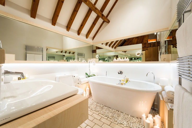 In this modern bathroom, a freestanding tub sits below a lofted ceiling, and a mirror that wraps around the wall makes the room feel larger. #ModernBathroom #Bathroom #Mirrors #FreestandingBathtub