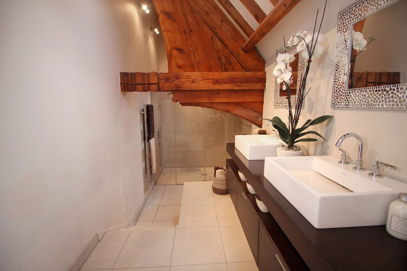 In this contemporary bathroom, the shower is stepped down from the vanity and original wood elements create a unique accent feature. #ContemporaryBathroom #WoodBeams #InteriorDesign